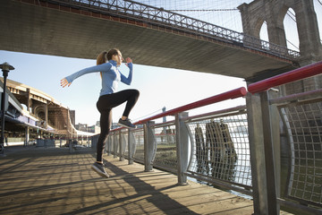 Caucasian runner stretching on waterfront, New York, New York, United States