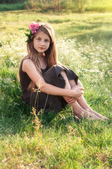 Girl with peony in her hair sitting on the field and looking at