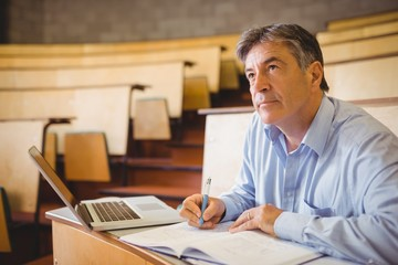 Thoughtful professor writing in book at desk