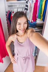 Changing room Asian woman taking selfie picture of her outfit. Young ethnic girl trying on a fashion dress taking a photo of herself in the fitting room or at home in her bedroom walk-in closet.