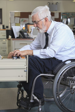 Caucasian businessman filing papers in office