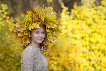 Attractive girl posing with a wreath of leaves. Portrait in autumn forest