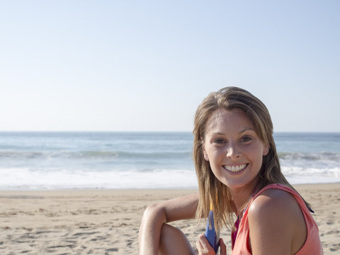 happy pretty woman smiling in the beach wearing a pink top with the sea and horizon in the background,