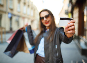 Happy beautiful woman with shopping bags and credit card in the