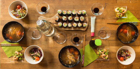 Japaneese lunch: sushi, shrimp salad with broad beans, soup, set table