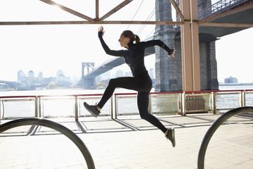 Caucasian runner jumping on waterfront, New York, New York, United States