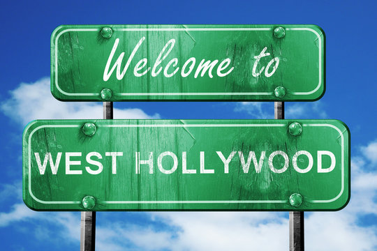 west hollywood vintage green road sign with blue sky background