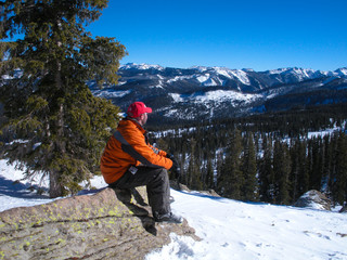 Man sitting in snow looking at mountains.