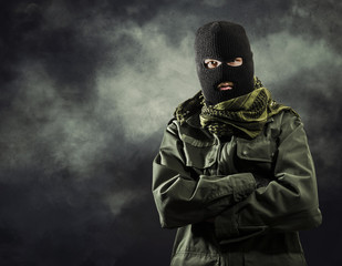 Portrait of masked terrorist in military jacket with smoke on background