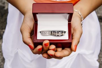 Mixed race girl holding wedding rings