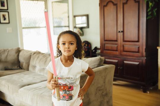 Mixed race girl holding light-saber in living room