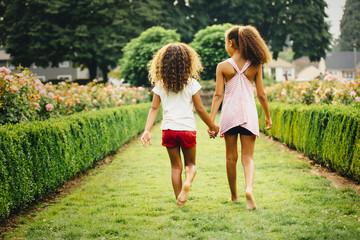 Mixed race sisters walking in garden