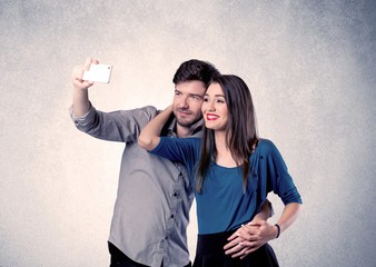Happy couple taking selfie with clear wall