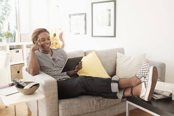 Mixed race man using digital tablet on sofa