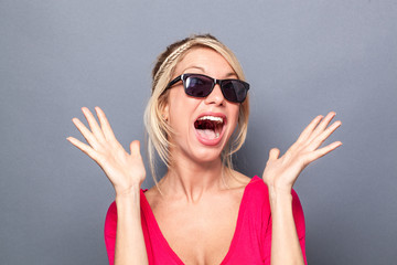 surprise concept - bubbly young blond woman looking like a star with her sunglasses, using both hands and facial expression for surprise and happiness, grey background studio