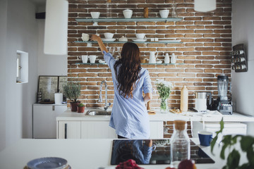 Caucasian woman reaching for dishes in kitchen