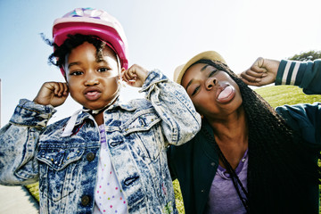 Black mother and daughter making faces