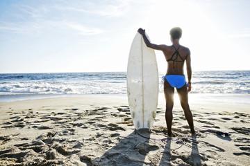 Black woman carrying surfboard on beach