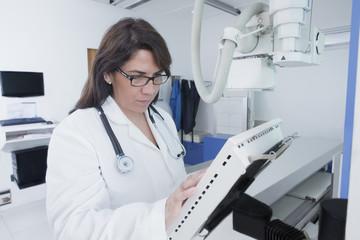 Hispanic doctor using x-ray in hospital