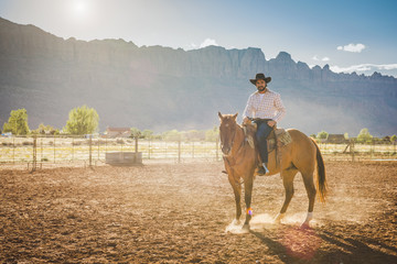 Hispanic man riding horse on ranch