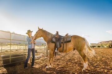 Hispanic woman petting horse on ranch