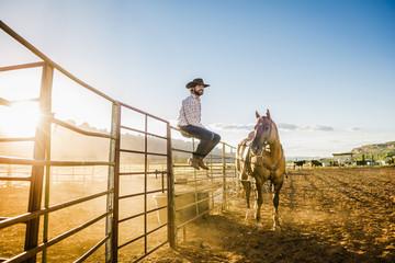 Hispanic man sitting on fence near horse