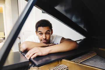 Mixed race man leaning on piano