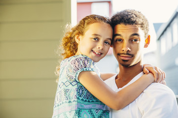 Mixed race brother holding sister outdoors