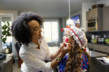 Mother painting face or daughter for Halloween
