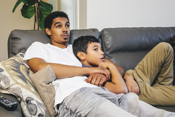 Mixed race brothers watching television on sofa