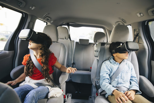 Mixed race children using virtual reality goggles in car