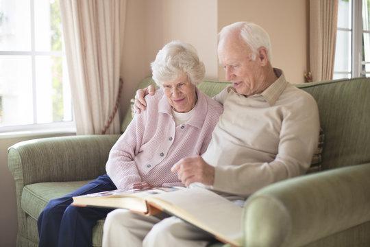 Older Caucasian couple looking at photo album