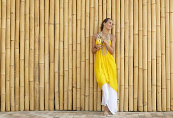 Pacific Islander woman drinking juice near bamboo wall