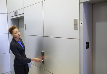 Mixed race businesswoman pressing elevator button