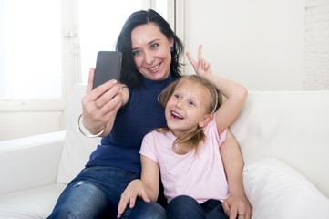 young happy woman with her little cute blond daughter taking selfie photo with mobile phone