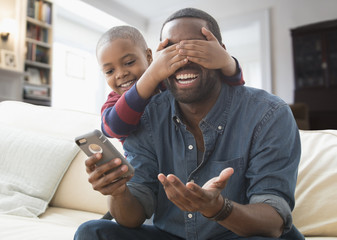 Boy covering eyes of father on sofa