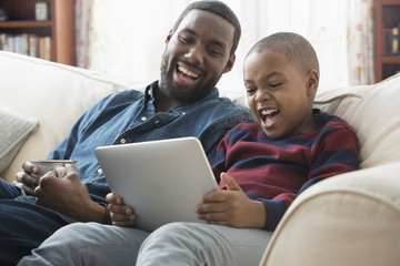 Father and son using digital tablet on sofa