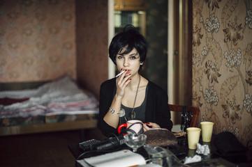 Caucasian woman smoking cigarette in bedroom