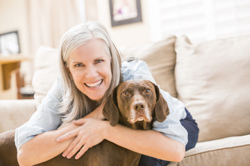 Caucasian woman hugging dog on sofa