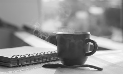Coffee cup with hot coffee on  wood background  in morning ,monochrome image