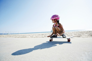 Mixed race girl riding skateboard at beach