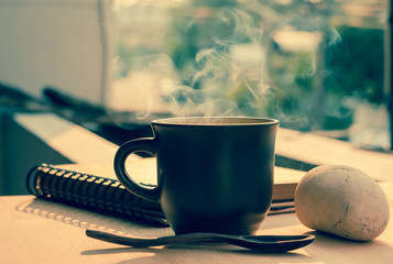 Coffee cup with hot coffee on  wood background  in morning,vintage image