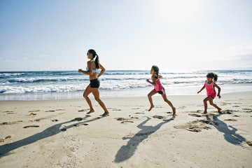 Mother and daughters running at beach
