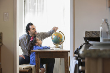 Hispanic father and daughter examining globe