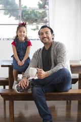 Hispanic father and daughter smiling at table