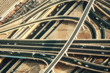 Aerial view of a highway junction with traffic in Dubai, UAE, at sunset. Sheikh Zayed road in Dubai.