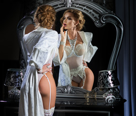The woman corrects make-up, standing in front of a mirror in an expensive, white lingerie and long robe