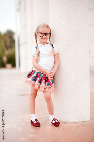 a58e7c405d2 Smiling kid girl 5-6 year old wearing backpack outdoors. Looking at camera.
