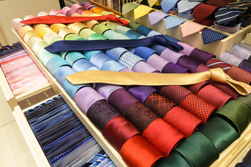 Different silk neckties on shelves in a store