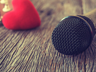 Music lover concept. A Black microphone on wooden plate with red heart.